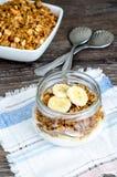 Granola, γιαούρτι και μια μπανάνα στο βάζο στο αγροτικό ύφασμα Στοκ Φωτογραφίες