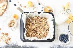 Granola σε ένα φύλλο μπισκότων με τα φρούτα και γάλα άνωθεν στο whi Στοκ φωτογραφία με δικαίωμα ελεύθερης χρήσης