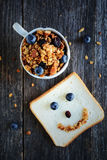 Granola with almonds and raisins. Breakfast image. Healthy homemade granola in cup on dark wooden table, american white sandwich bread with funny face made of Stock Photography