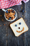 Granola with almonds and raisins. Breakfast image. Healthy homemade granola in cup on dark wooden table, american white sandwich bread with funny face made of Stock Photos