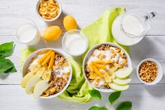 Free Granola And Vegetarian Yogurt With Slices Of Apple, Apricot, Banana And A Jug Of Milk On A White Wooden Background. Healthy Royalty Free Stock Photo - 181362815