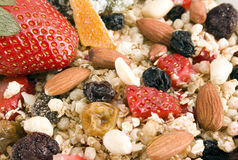 Granola background. Granola: oats, rice, honey, peanuts, almonds, wax berry, white and red raisins, glazed orange peel and strawberries. Focus from center to the Stock Photos