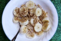 Granola and bananas. A spoonful of granola, with a slice of banana and cream with the bowl with the cereal and bananas in the background Stock Images