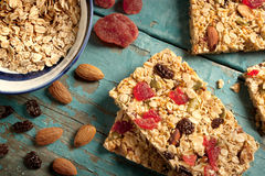 Granola bar on a blue wooden table. With ingredients Royalty Free Stock Image