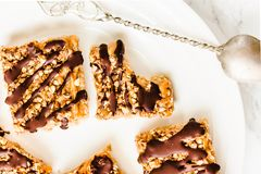 Granola bar cake with date caramel and chocolate. Healthy sweet dessert snack. Cereal granola bar with nuts, fruit and berries on. A white marble table.Top view stock images