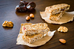 Granola bar or energy bar on brown background. Granola bar or energy bar with oats, dates and nuts on brown wooden background Royalty Free Stock Photos
