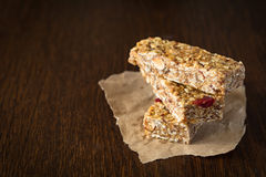 Granola bar or energy bar on brown background. Granola bar or energy bar with oats, dates and nuts on brown wooden background Stock Images
