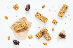 Granola bar or energy bar on white background. Granola bar or energy bar with oats, dates and nuts on white wooden background, top view Royalty Free Stock Photography