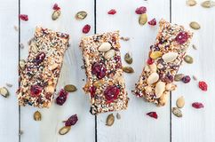 Granola bar on wooden table. Granola bar. Healthy sweet dessert snack. Cereal granola bar with nuts, fruit and berries on a white wooden table. Top view Royalty Free Stock Images