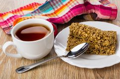 Granola bar in plate, tea in cup, teaspoon, checkered napkin. On wooden table Royalty Free Stock Image