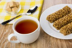 Granola bar in plate, tea, teaspoon, bowl with sugar. On wooden table Royalty Free Stock Images