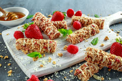 Granola bar with strawberries, raspberry honey and white chocolate on cutting board Stock Image