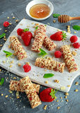 Granola bar with strawberries, raspberry honey and white chocolate on cutting board Stock Photography
