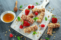 Granola bar with strawberries, raspberry honey and white chocolate on cutting board.  Stock Photography