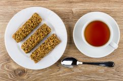 Granola bar in plate, cup of tea on saucer, teaspoon. Granola bar in white plate, cup of tea on saucer, teaspoon on wooden table. Top view Royalty Free Stock Images