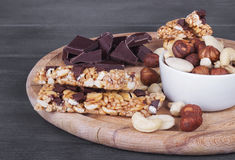 Granola bars, nuts, and  chocolate on  cutting board. Stock Photos