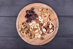 Granola bars, nuts, and  chocolate on wooden cutting board. Royalty Free Stock Photo