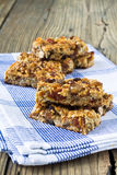 Granola bars with nuts and dried fruits. On wooden background stock photography