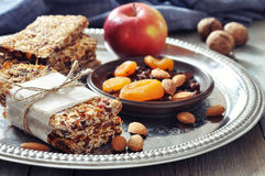 Granola bars. On plate with nuts and dried fruits on wooden background Royalty Free Stock Photo