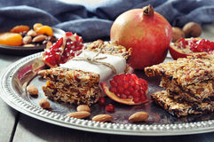 Granola bars. On plate with nuts, pomegranate and dried fruits on wooden background Royalty Free Stock Images