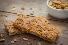 Granola bars on wooden table and peanuts Royalty Free Stock Photos