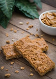 Granola bars on wooden table and peanuts in bowl Stock Photo