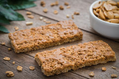 Granola bars on wooden table and peanuts in bowl Royalty Free Stock Photo