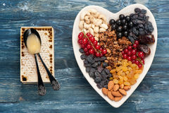 Granola, berries, nuts, dried fruit and honey comb. Healthy breakfast ingredients. Top view Stock Images