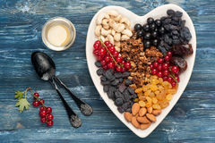 Granola, berries, nuts, dried fruit and honey. Healthy breakfast ingredients. Top view Stock Photo