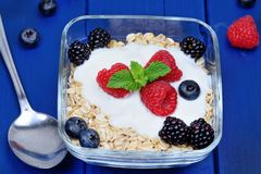 Granola with berries and yoghurt on wooden table stock photography