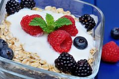 Granola with berries and yoghurt in a transparent bowl on wooden table stock images