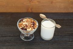 Granola with berries and yogurt on a black wooden table. Traditi. Onal American Breakfast Stock Photos
