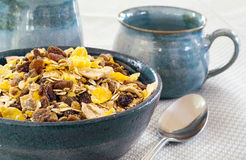 Granola in a blue bowl, ceramic mugs in the background Stock Photo