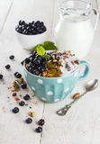 Granola with blueberry, mint, honey and milk in blue bowl with m. Ilk jug on a white table Stock Photo