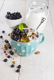 Granola with blueberry, mint, honey and milk in blue bowl with m. Ilk jug on a white table and metal spoon Stock Photos
