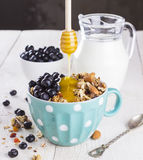 Granola with blueberry, mint, honey and milk in blue bowl with milk jug on a white table and metal spoon Stock Photos