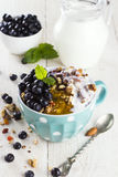 Granola with blueberry, mint, honey and milk in blue bowl on a w. Hite table Stock Images
