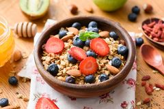 Granola bowl with fresh strawberries, blueberries, dried goji berries and almonds on wooden table. Concept of healthy lifestyle, healthy eating, dieting Stock Photos