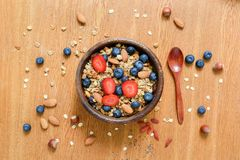 Granola bowl with fresh strawberries and blueberries on wooden table. Flat lay. Concept of healthy lifestyle, healthy eating, dieting and balanced meal Stock Photography