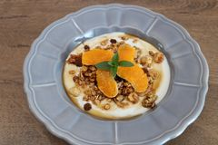 Granola bowl with soy yogurt,maple syrup, orange slices and mint leaves stock photo