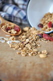 Granola bowl spilling on wooden board Royalty Free Stock Photo