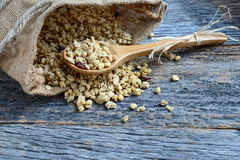 Granola in Burlap Sack Spilling onto Wood Background Royalty Free Stock Images
