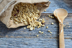 Granola in Burlap Sack Spilling onto Wood Background Stock Photo