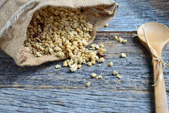Granola in Burlap Sack Spilling onto Wood Background Stock Photos