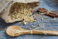 Granola in Burlap Sack Spilling onto Wood Background Royalty Free Stock Photo