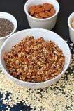 Granola casalingo in ciotola bianca con la mandorla ed i semi su fondo nero Fotografia Stock
