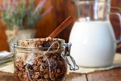 Granola casalingo con i dadi, mirtilli rossi ed albicocche secche e una brocca di latte Fuoco selettivo, spazio della copia fotografie stock