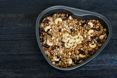 Granola with cashews in a baking sheet. Black wooden table.  Royalty Free Stock Images