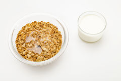 Granola cereal isolated on white backgroung. Granola cereal with dried frutis, nuts and honey in a bowl and milk cup isolated on white backgroung Stock Image