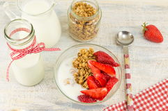 Granola cereals, fresh strawberries and bottle of milk Stock Photo
